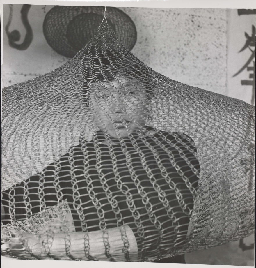 Untitled (Ruth Asawa on bed looking out of looped-wire sculpture ...