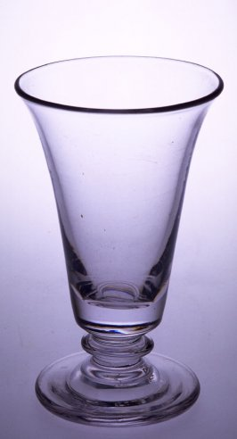 Syllabub glass clear in color; round foot; short stem with flared lip