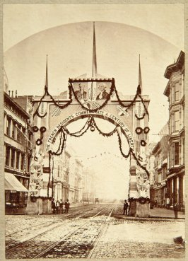photo of archway over cobblestone street with trolly tracks: The French Residents Commemorate a Century of Liberty