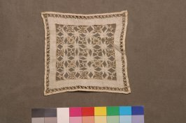 One of nine embroidered square doilies