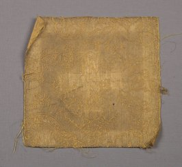 Fragment of cream linen with embroidery in yellow and green