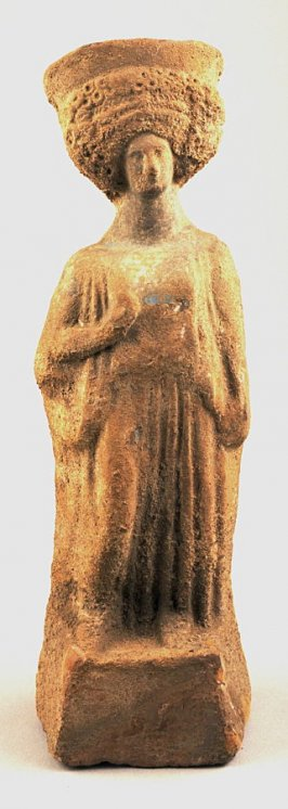 Standing draped female figure with elaborate coiffure