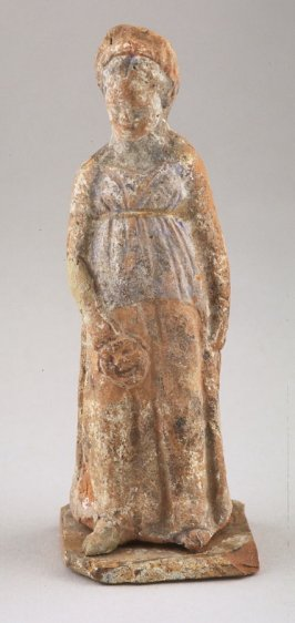 Small standing draped female figure holding mask in right hand