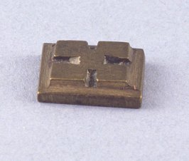 "Goldweight with raised ""X"" shape"