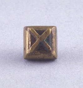 "Goldweight with raised ""X"" design"