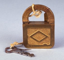 Padlock with piece of metal and key attached