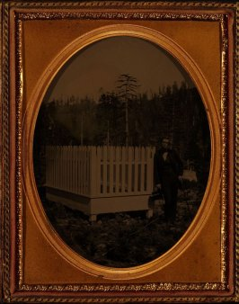 Untitled (Undertaker standing next to a picket fence surrounding a grave, Auburn, California)
