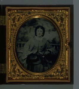 Portrait of seated woman holding hat, against painted scenic backdrop in S. Peck & Co. union case with round belt design