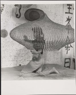 Untitled (Ruth Asawa on bed kneeling inside looped wire sculpture)