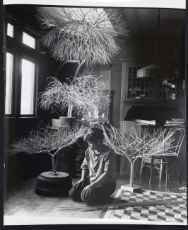 Untitled (Ruth Asawa kneeling on floor of dining room with tied wire sculpture)