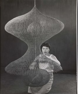 Untitled (Ruth Asawa kneeling behind looped-wire sculpture)