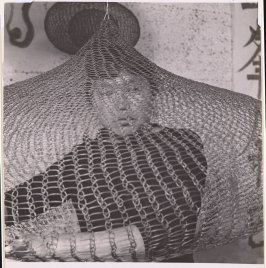Untitled (Ruth Asawa on bed looking out of looped-wire sculpture)