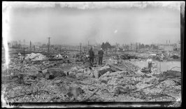 Untitled (Two men pose while looking at this general scene of ruin after the earthquake and fire)