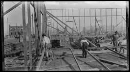 Untitled (Men work to rebuild the city surrounded by the ruins left by the earthquake and fire)