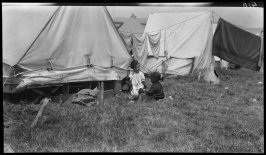 Untitled (Children play in the grass around a tent camp in post fire and earthquake days)