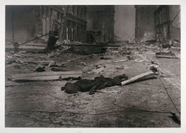 Untitled (Charred corpse in street amid rubble and ruin)