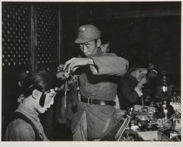 By the light of a kerosene lamp a young Chinese captain is made up by one of his soldiers to play a female part in a Chinese opera performance staged by soldiers of the second army in Shunning, Yunnan. 1944