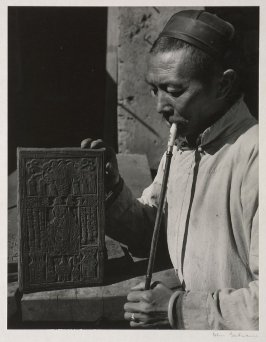 A village artist of Yunnan with one of his wood blocks from which he makes prints to be sold as funeral papers or as protection against evil spirits.