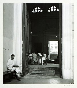 An assistant guards the entrance to an examination classroom of the University of Calcutta where students are writing their final papers.