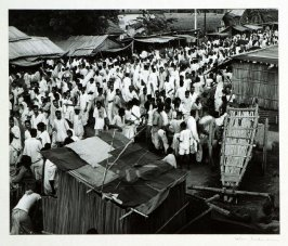 Crowds mill around a village bazaar, Bengal Province. Shops are bamboo made stands and customers are served outside.