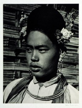 Burmese amateur actor, cast in one of the many epic plays which are performed on an open air bamboo stage in the center of the village. The elaborate earrings are part of the headdress. A British silver coin serves as button for the costume.