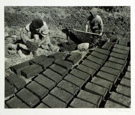Women making mud bricks, the universal construction material in Yunnan. Bricks are made from mud and straw binder which is poured into wooden forms, they are laid out for sun drying.