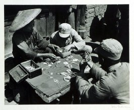 The wife of a local silversmith selling various jewelry at an open market in the small town of Yunnanyi. The soldier in his cotton-padded uniform has selected an enameled pendant. Brooches, necklaces, bracelets, hair pins, ear and finger rings, all of sil