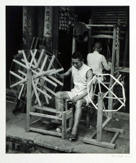 The manufacture of cotton is still a home industry in some parts of Hunan Province. This cotton spinning wheel, shown in a small shop in Chihkiang, is turned by a wooden crank. In the background another workman operates a low-warp loom.
