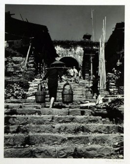 Water carriers climbing up the stairs from the river in Chenki, Hunan Province. In the background the gate through the old city wall leading to the inner town.