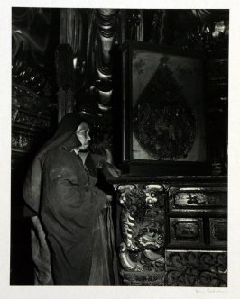 A Buddhist abbot in ceremonial robe stands beside a temple altar. The glassed case contains a jewelled Tibetan painting.