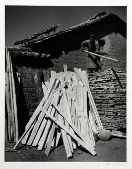 A lumber merchant of Yunnan sorting stock in his courtyard.