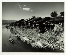 Piled dwellings and lumber floats line the Yuan River in Ankiang, Province of Hunan. A sampan moves upstream while soldiers wash their laundry.