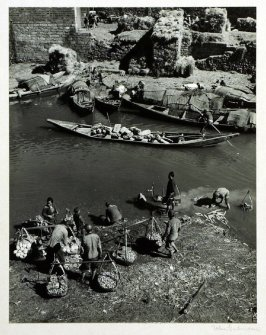 Vegetables are carried on shoulder poles to the canal where they are washed in the same waters through which a large part of Kunming's traffic moves. The boatman is taking his heavy load of rocks to a building ground, while the women in the background kee