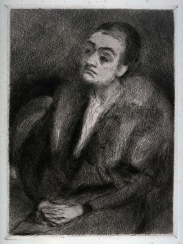 Woman seated, hands folded, eyes left