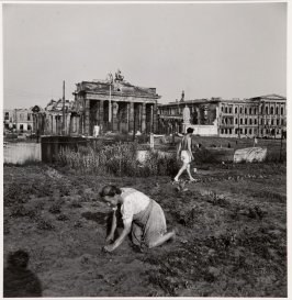 Woman planting near Brandenberg Gate, Berlin