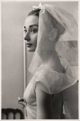 "Audrey Hepburn in a wedding dress with cigarette on the set of ""Funny Face,"" Paris, 1956"