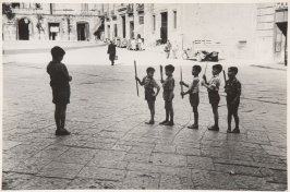 Children playing as soldiers, Italy