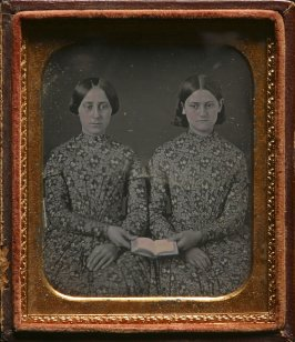 Untitled (Two sisters in identical dresses holding a book)