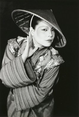 Lisa Jear in a Kaisik coat and collar with a conical straw hat