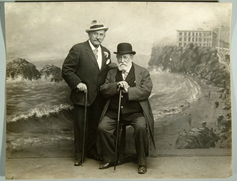 photo plus reproductions of two men sitting in front of painted back drop of Cliff House