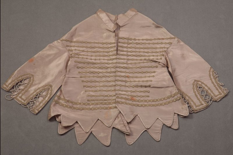 Child's Jacket :beige-tan w/green braid in horizonal lines on front, arches on sleeves is scalloped