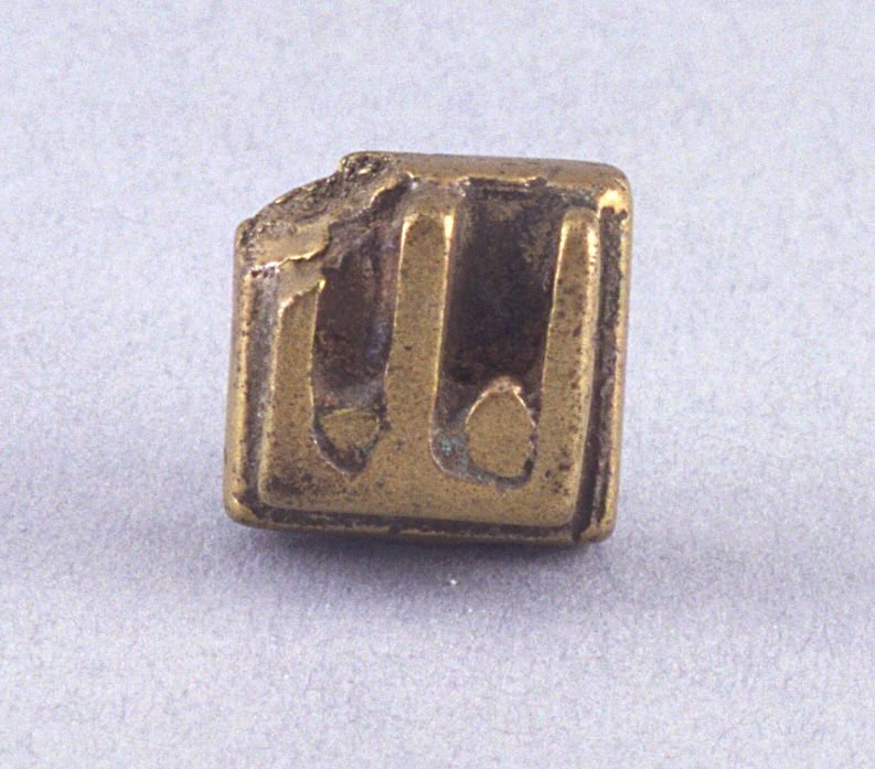 "Goldweight with raised ""E"" shape"