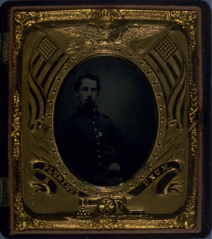 Portrait of seated Union soldier in Union case with crossed cannons and other military symbols by Scovill Mf'g Co.