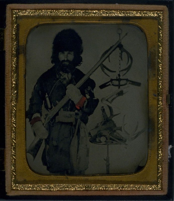 Portrait of hunter/trapper with gun in Union case of man standing astride fallen deer and waving hat