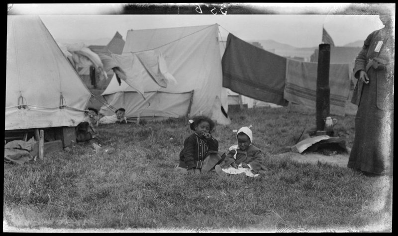 Untitled (Two children sit in the grass in the front of some tents in the post fire and earthquake days)