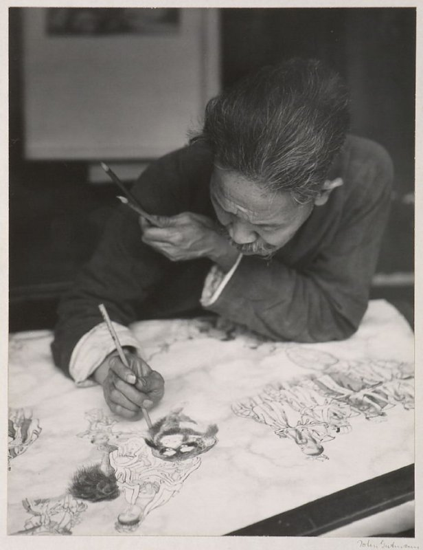 Artist in his shop painting a scroll in the manner of traditional Chinese art.