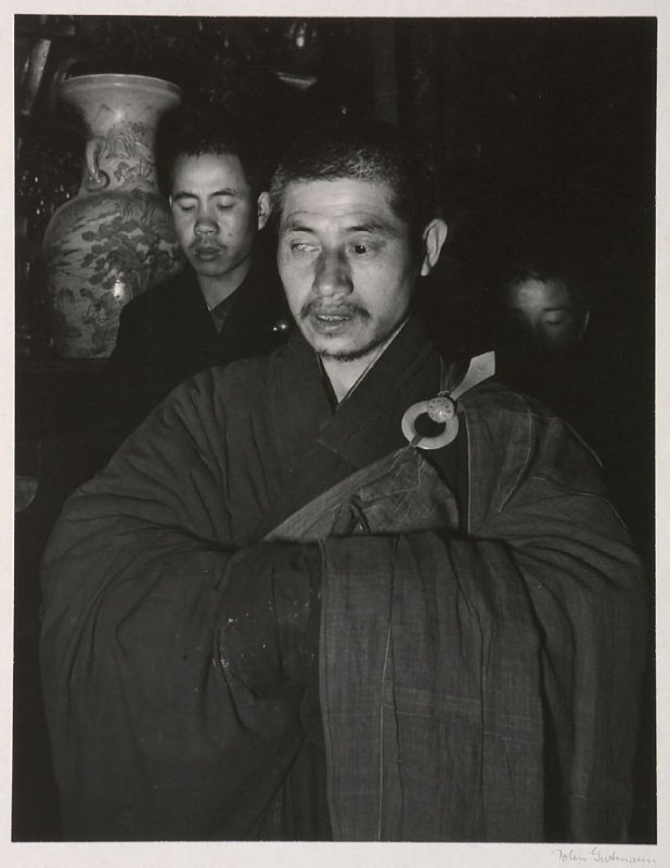 A one-eyed Buddhist monk and neophytes chanting a monotonous liturgy.