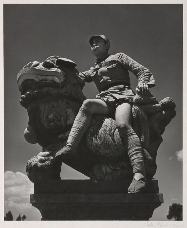A young Chinese soldier seated on a stone lion.