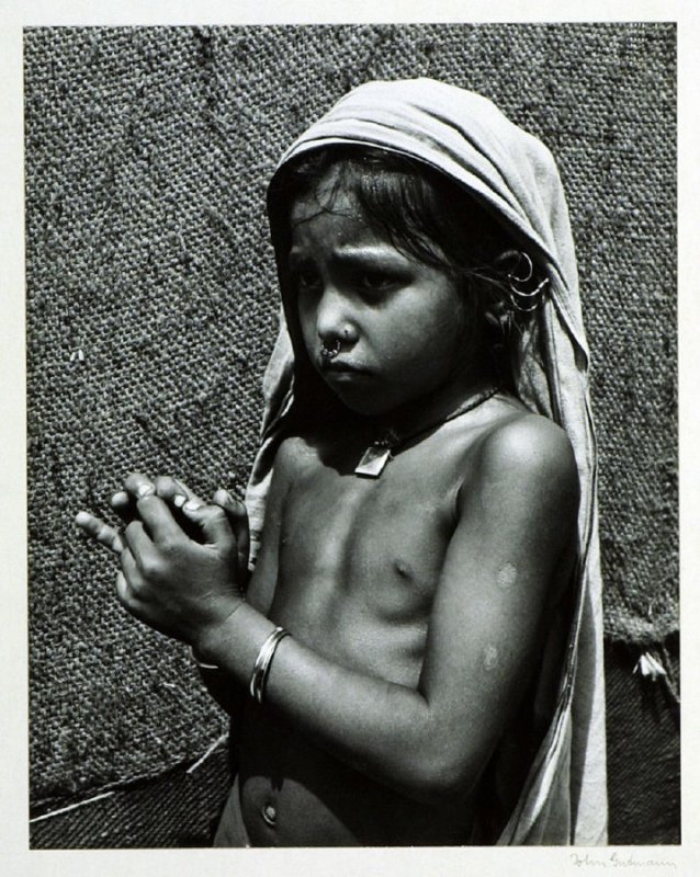 A Bengalese child with a tabiz around her neck, an amulet, worn by Hindus and Moslems alike. Ears and noses of girls are pierced for jewelry at a very early age.