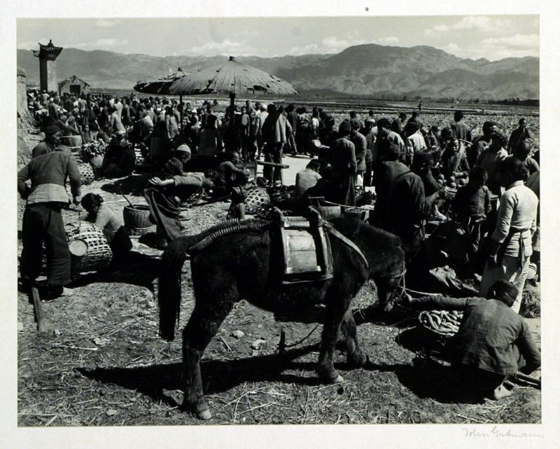 Large crowds always attend weekly markets such as this one held in Paoshan, a town on the old Burma Road, halfway between the Meekong and Salween Rivers. Upon the Mongolian pony is placed a wooden pack saddle on which products of the farm are carried to t